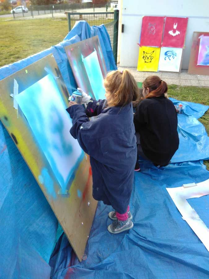 Atelier Graffiti pour réaliser des posters à partir de bombes de peintures et pochoirs.